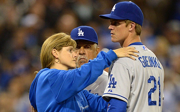 Dodgers head athletic trainer checks on Zack Greinke after his collision with Carlos Quentin. Results say he Greinke broke his collarbone.